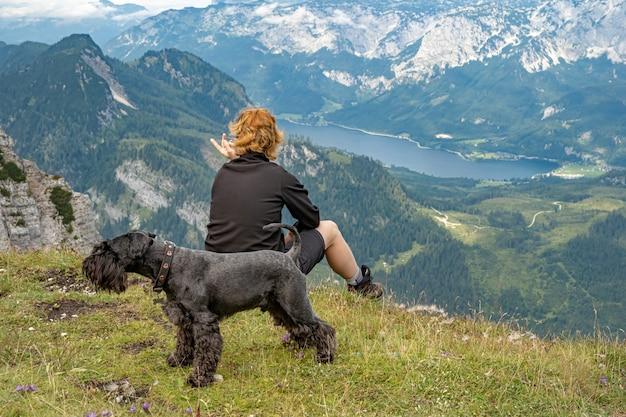 Wandelaars in de oostenrijkse alpen lopen op bergwandelpaden in het bos rond de meren met zwarte hond