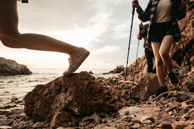 Wandelaars lopen op de rotsen in het midden van de zee. teamwork en avontuur, reisconcept.