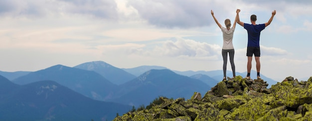 Wandelaars met opgeheven armen op bergtop.