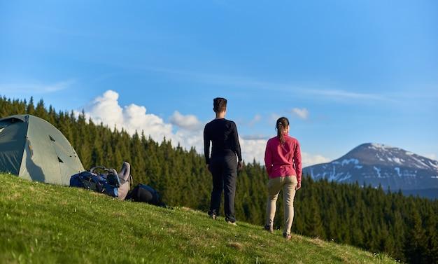 Wandelaars met rugzakken bovenop een heuvel bij tenten