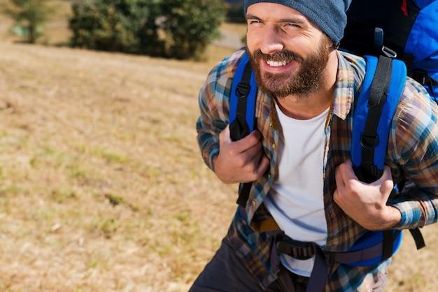 Wandelaars zijn het gelukkigst! close-up van een knappe jongeman die een rugzak draagt en ernaar uitkijkt met een glimlach