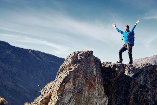 Wandelaarvrouw met rugzak op rots van een berg en genietend van zonsopgang. reizen levensstijl succes concept