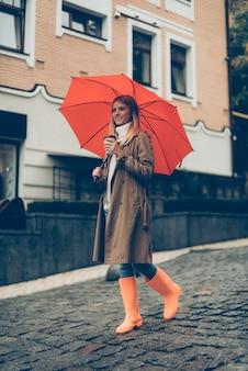 Wandelen door de stad. volledige lengte van aantrekkelijke jonge lachende vrouw in rubberen laarzen met paraplu en koffiekopje terwijl ze op straat loopt