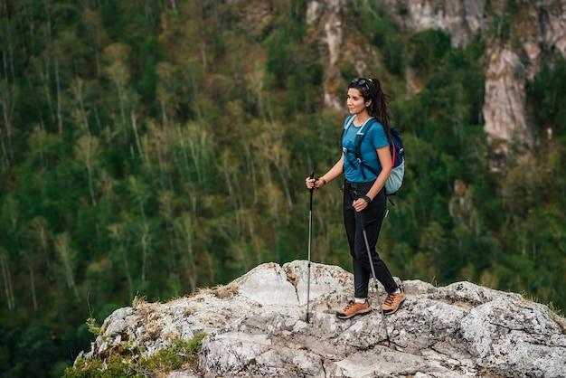 Wandelen in de bergen. het concept van actieve recreatie. reizende vrouw met een rugzak op de achtergrond van bergen. vrouwelijke reiziger met een rugzak wandelen in de bergen. ruimte kopiëren