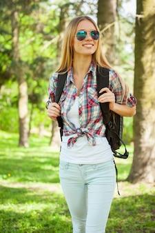 Wandelen in een bos. mooie jonge vrouw die haar rugzak draagt en glimlacht tijdens het wandelen in een bos