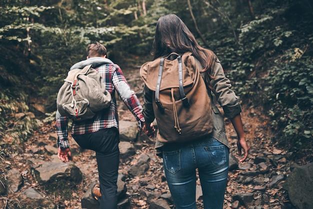 Wandelen is soms erg zwaar. achteraanzicht van een modern jong stel dat handen vasthoudt en omhoog beweegt terwijl ze samen wandelen in het bos