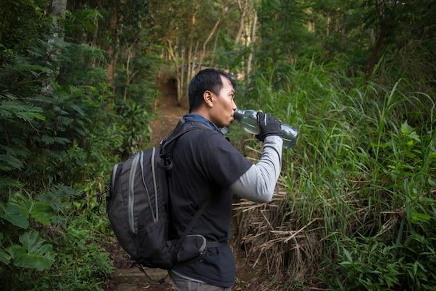 Wandelen man ontspannen en drinkwater uit de fles na een trektocht in de bergen