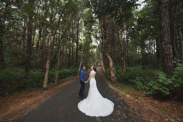 Wandelen met de jonge bruid en bruidegom in het bos