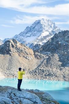 Wandelen op de berg op herfstdag man die foto maakt van een geweldig landschap op de telefoon