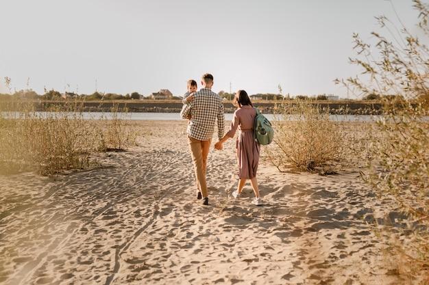Wandelen op het zandstrand van de rivier en gelukkige familie. vader, moeder zoontje op handen houden en samen gaan. achteraanzicht. familiebanden concept.