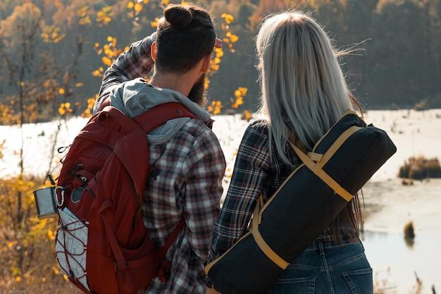 Wandelen reizen achteraanzicht van paar kijken naar bos en moeras herfst natuur landschap