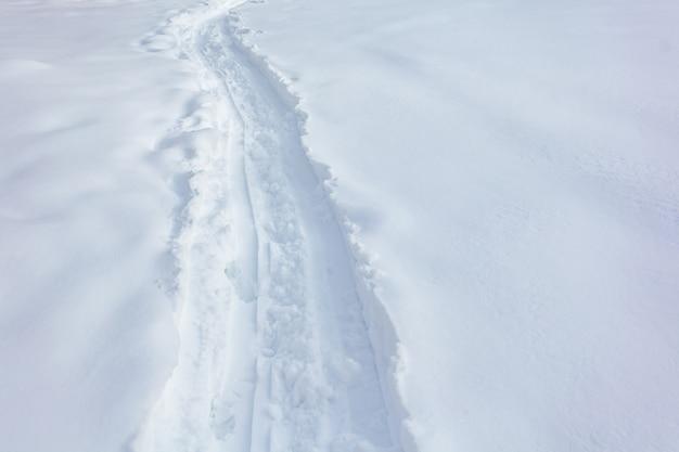 Wandelen volgt voetstappen in de verse sneeuw, winter