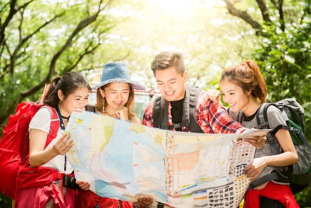 Wandelen - wandelaars kijken naar kaart. paar of vrienden navigeren samen lachen gelukkig tijdens camping reizen wandelen buiten in het bos. jonge gemengd ras aziatische vrouw en man.