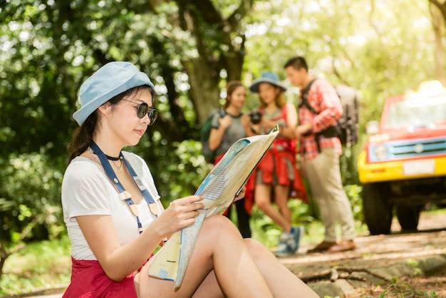 Wandelen - wandelaars kijken naar kaart. paar of vrienden navigeren samen lachen gelukkig tijdens camping reizen wandelen buitenshuis in het bos. jonge gemengd ras aziatische vrouw en man.
