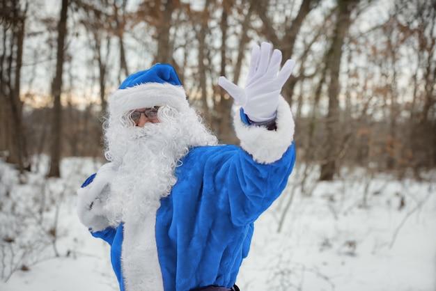 Wandelend door het winterbos, zwaait met zijn hand santa claus in blauw pak met kerstcadeautjes