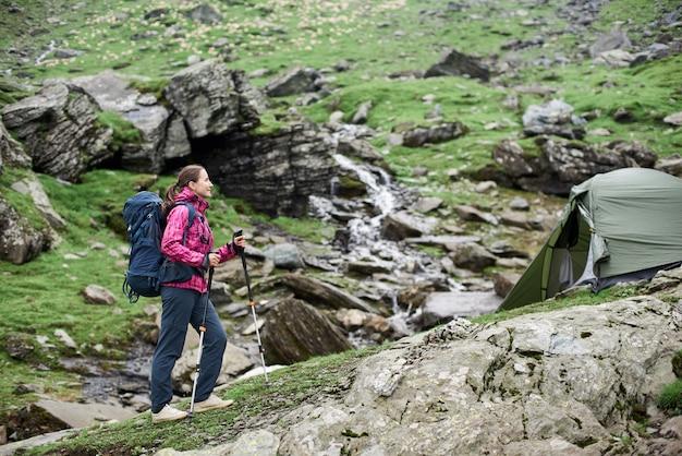 Wandelend meisje met wandelstokken en een rugzak in de buurt van tent geniet van een prachtig uitzicht op een rotsachtig terrein van bergen.