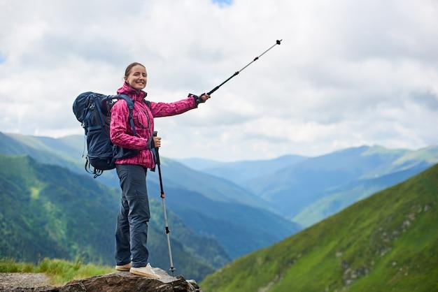 Wandelend meisje met wandelstokken en een rugzak staat op een rots met een onscherpe achtergrond van de machtige bergen