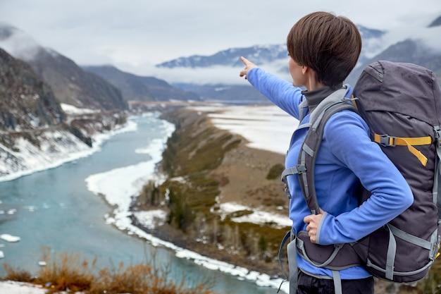 Wandelende glimlachende vrouw met een rugzak in bergen. mooie jonge vrouw reist in de bergen