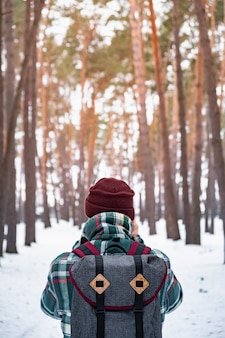 Wandelende mannelijke persoon in de winterbos. mens die in geruit de winteroverhemd in mooi sneeuwbos loopt