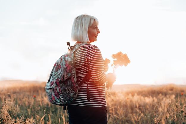 Wandelende vrouw die in het veld staat en naar de horizon kijkt met een prachtige lucht bij zonsondergang. prachtig landschap, vrijheid, de eenheid van mens en natuur