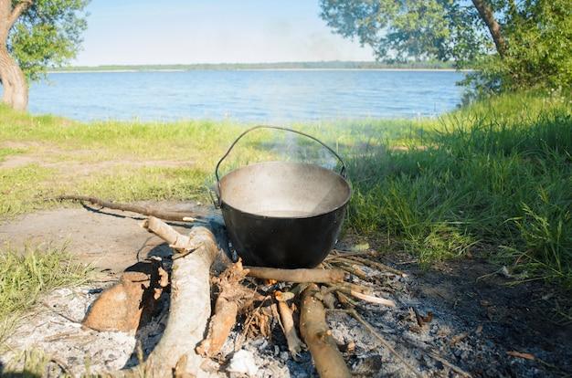 Wandeling naar de natuur. eten koken in een pot boven het vuur op een zonnige zomerdag. kampeereten aan de oever van het meer.
