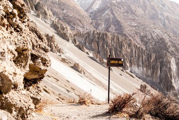 Wandelpad in bergen met bergheuvels en waarschuwingsbord dat zegt - aardverschuiving is