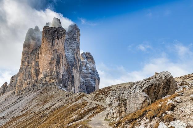 Wandelpad met uitzicht op verbazingwekkende bergen van tre cime di lavaredo bedekt met sneeuw in de herfst, dolomieten, italië