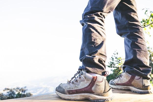 Wandelschoenen in actie op een bergweg van de woestijnsleep. close-up van mannelijke wandelaarsschoenen.