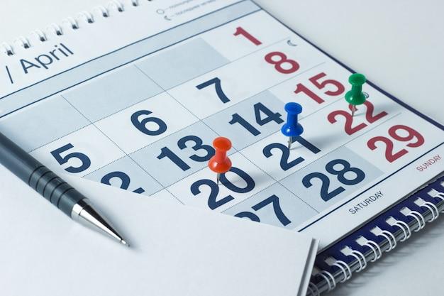 Wandkalender en pen, belangrijke dagen zijn gemarkeerd met knoppen