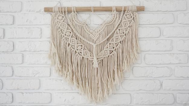 Wandpaneel in de stijl van boho gemaakt van katoenen draden in naturel kleur op een witte bakstenen muur. prachtig boho macramé wandpaneel voor een gezellige sfeer