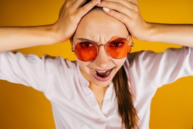 Wanhoop en afgrijzen op het gezicht van een meisje met een bril, haar hoofd in haar handen geklemd. achtergrond geel