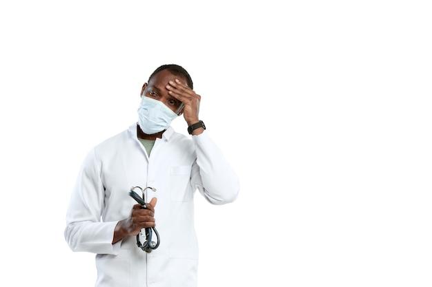 Wanhoop, moe. mannelijke jonge arts met een stethoscoop en gezichtsmasker op witte studio.