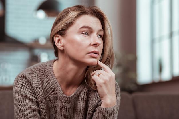 Wanhopig. depressieve blonde rijpe vrouw voelt zich wanhopig na ruzie met echtgenoot