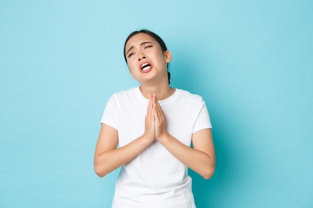 Wanhopig ongemakkelijk verdrietig aziatisch meisje smeekt om hulp, smeekt en huilt, smeekt om een lastig leven, staat blauwe muur in nood, rouwt of vraagt om verontschuldiging