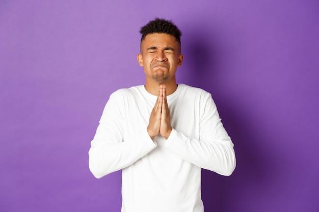 Wanhopige afro-amerikaanse man smeekt bij god, hand in hand in gebed en smekend
