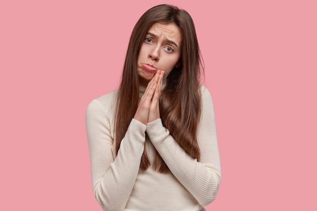 Wanhopige, bedroefde jonge charmante vrouw met lang haar, houdt handpalmen in gebed, vraagt god om dromen waar te maken, smeekt om gunst
