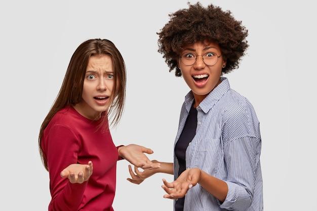 Wanhopige gefrustreerde twee vrouwen van gemengd ras spreiden hun handen, staan zijwaarts, kijken verontwaardigd, model tegen een witte muur. dus wat te doen? verbaasde multi-etnische meisjes schreeuwen luid