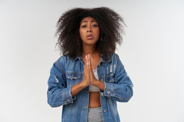 Wanhopige gekrulde donkere vrouw in witte top en jeansjas die handen opheft in biddend gebaar, met droevig gezicht, staande over witte muur