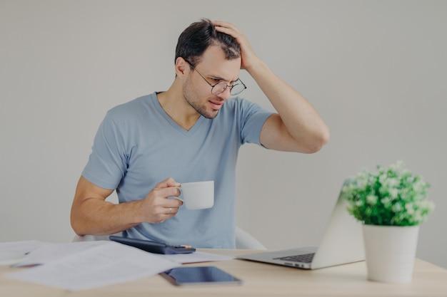 Wanhopige jonge man heeft financiële crisis, krabt hoofd in spanning