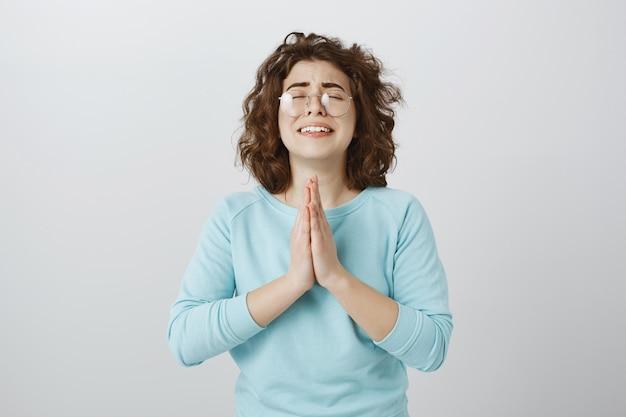 Wanhopige jonge vrouw die hulp aan god vraagt, hand in hand bidt, smeekt of wens doet