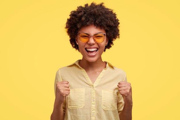 Wanhopige jonge vrouw met afro kapsel, fronst gezicht en klemt tanden, kijkt boos, heeft geïrriteerde uitdrukking