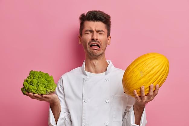 Wanhopige mannelijke chef-kok in uniform, huilt en uit negatieve emoties, houdt broccoli, meloen