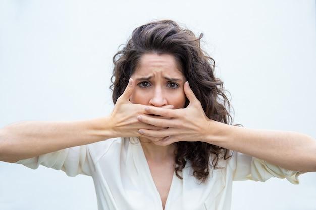Wanhopige ongelukkige vrouw die mond behandelt met beide handen