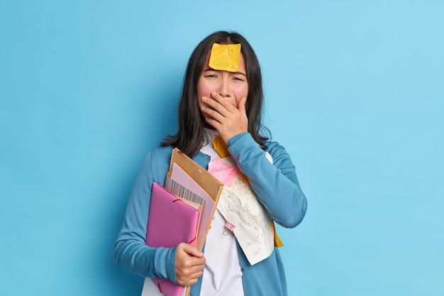 Wanhopige studente huilt ongelukkig bedekt mond voelt overstuur heeft sticker met afbeelding geplakt op voorhoofd heeft deadline voor voorbereiding op examens.
