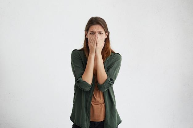 Wanhopige vrouw met donkere ogen die een bruin t-shirt en een groen jasje draagt, gaat huilen