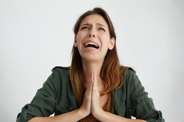 Wanhopige vrouw smeekt om genade en huilt. emotionele vrouw die haar handpalmen tegen elkaar houdt en er treurig uitziet terwijl ze om iets smeekt. huilende teleurgestelde vrouw die om vergeving vraagt