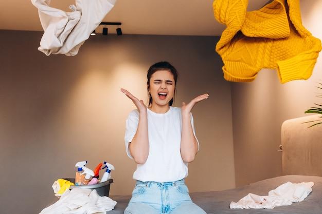 Wanhopige vrouw zittend op de bank in rommelige kamer en schreeuwen en kleren trowing vanwege moe schoonmaken en wassen