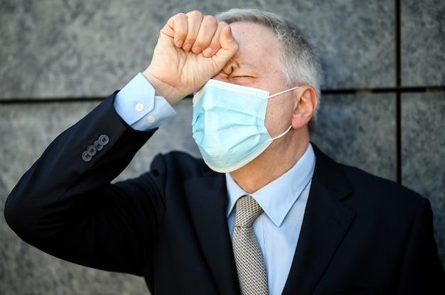 Wanhopige zakenman die een masker draagt tegen het coronavirus, het concept van de financiële crisis