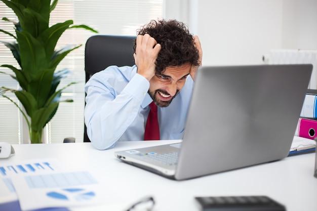 Wanhopige zakenman die in zijn bureau werkt