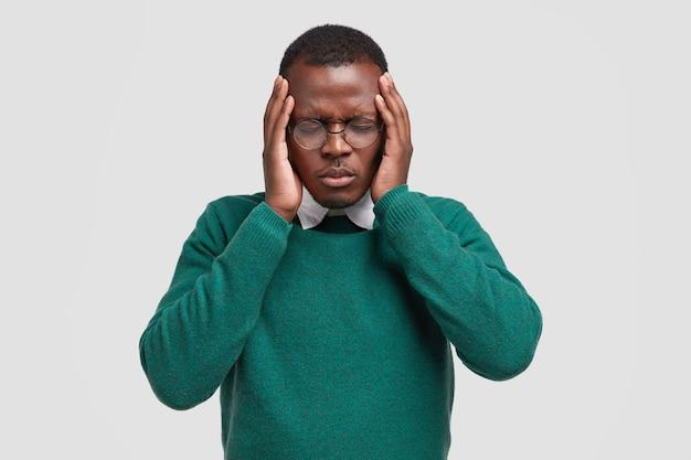 Wanhopige zwarte jongeman houdt beide handen op het hoofd, sluit de ogen, lijdt aan migraine, heeft droevige vermoeidheid, gezichtsuitdrukking